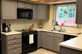 Grey Kitchen Cabinet Design Combined With Black Appliances And White Tiles Wall Solid Countertop On Ceramict Floor