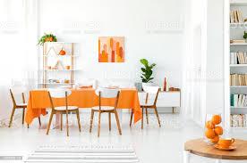 weiß und orange esszimmer mit gemälde an der wand regal in der ecke und grüne pflanze im topf stockfoto und mehr bilder behaglich