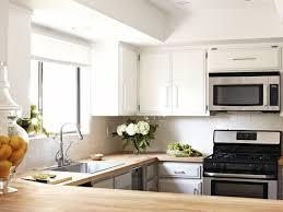 kleine küche in u form mit weißem fliesenspiegel und holz