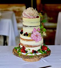 Naked Wedding Cake Covered In Fresh Flowers And Fruit Farm Rustic