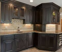 distressed black kitchen cabinets with counter lighting