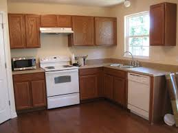 White Cabinets Dark Grey Countertops by White Kitchen Wall Paint Combined By Brown Wooden Kitchen Cabinet