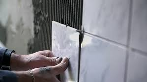 Ceramic Tile For Bathroom Walls by Ceramist Puts Tile On The Wall Professional Ceramist Is Laying