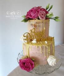 Two tier pink semi wedding cake with white chocolate glaze and fresh flowers Topped off with a few meringue kisses x