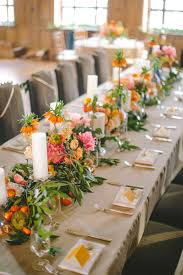 Long Wedding Head Table With Orange Place Cards Greenery And Fruit Garland