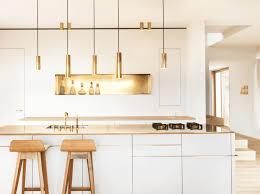 white wooden kitchen island gold pendant light gold faucet
