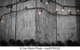 Christmas Lights And Pine Cones On Rustic Wood Background Stock Photo