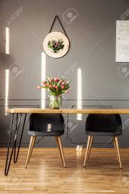 graue stühle am holztisch mit blumen im esszimmer mit dekor auf der wand