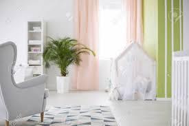 geräumiges weißes babyzimmer mit sessel pflanze und krippe