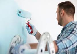 Man With Roller Painting Wall Blue