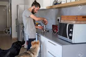 Young Hipster Man Making Coffee At Home Kitchen With His Pet Stock