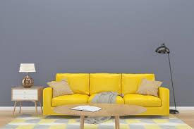 graue wand mit gelbem sofa auf holzboden 1226977 stock foto