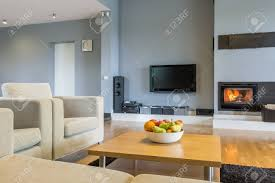 geräumiges wohnzimmer in grau mit sofa sessel kleiner tisch tv und kamin