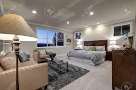 graue töne schlafzimmer interieur mit queensize bett mit sitzecke mit beige leinen sofa und glas cocktail tisch auf grau flauschigen teppich