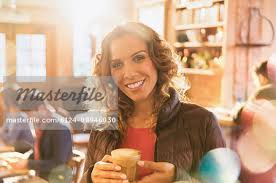 Portrait Smiling Woman Drinking Iced Coffee In Cafe