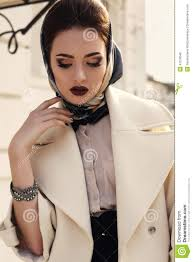 beautiful in elegant beige coat and silk scarf on head stock