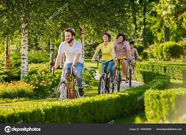 Happy Friends Cycling In City Park Stock Photo
