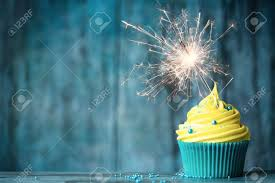 Cupcake with yellow buttercream and a sparkler Stock