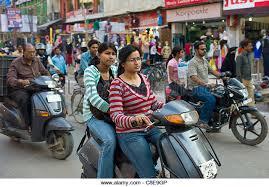 Young Indian Girls Ride Motor Scooter In Street Scene City Of Varanasi Benares