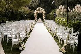 White Aisle And Chairs Leading To Floral Chuppah