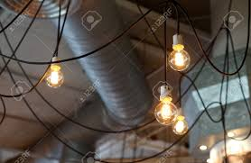 hanging light bulb and black cable with exposed ceiling background