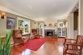 schönes wohnzimmer mit vintage möbeln und roten teppich auch gemauerten kamin zwei regale und große französisch fenster northwest usa