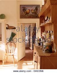 Display Of Pottery On Small Pine Dresser In Country Dining Room With Windsor Chair Beside Open