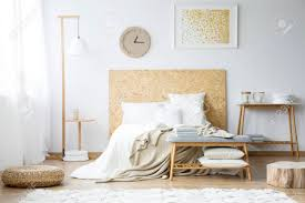 papieruhr und goldmalerei an der wand über dem bett mit beige bettlaken im schlafzimmer mit hocker und holzmöbeln