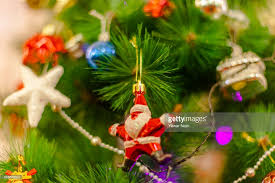 A Toy Santa Claus Hangs On Christmas Tree Inside The Holy Family Catholic Church During