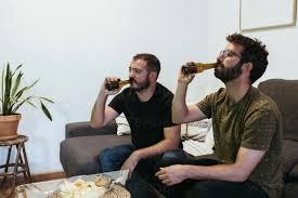 männliche freunde trinken bier während sie zu hause im
