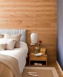 Mesilla de noche en madera sobre el suelo y pared de cabecero