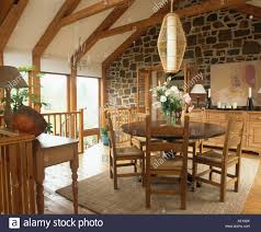 Cylindrical Light Above Circular Mahogany Dining Table And Rush Seated Chairs In Upstairs Room With Exposed Stone Wall