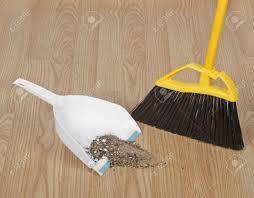 broom sweeping up dirt into dust pan on hardwood floor stock photo