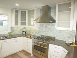 white kitchen with glass tile backsplash cabinet and countertop