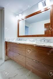 das elegante badezimmer verfügt über einen doppelwaschtisch mit einer arbeitsplatte aus weißem grauem marmor und einem unterbau aus weißem rechteck