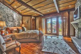 Rustic Elegant Bedroom With Stone Fireplace Wall And Wood Floors
