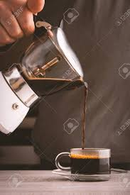 Man Pouring Coffee Into A Glass Cup Vertical Stock Photo