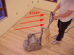 sanding a new hardwood floor with a rental drum sander