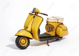 Old Classic Vintage Yellow Motor Scooter With A Wide Footboard And Saddle Style Seat Standing Upright
