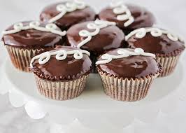 A White Cupcake Stand Full Of Homemade Hostess Cupcakes Made Using This Recipe With Chocolate Icing