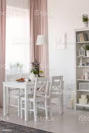 echtes foto esszimmer interieur mit stühlen und weißen tisch mit lavendel und frühstück fenster mit vorhängen und rack mit dekor stockfoto und