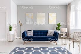 ein elegantes marineblau sofa in der mitte ein helles wohnzimmer interieur mit gold metall beistelltische und drei gemälde auf eine graue wand echtes