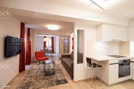 elegantes wohnzimmer mit roten designer sessel und moderne weiße küche stockfoto und mehr bilder architektur