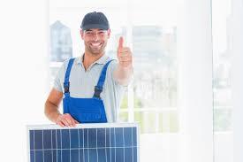 le bureau solaire ouvrier avec le panneau solaire faisant des gestes des pouces dans