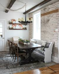 Brick Wall Dining Area With Wood Beams A Farmhouse Table And Pew