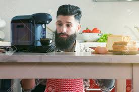Bearded Man Making Morning Espresso With Coffee Machine While Breakfast At Kitchen Stock Photo