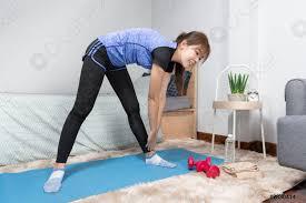 foto auf lager asiatin macht zu hause fitness und auf einer fitnessmatte macht sport zu hause im wohnzimmer sportliches mädchen