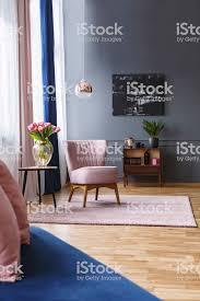 rosa stuhl neben den tisch mit blumen im eleganten wohnzimmer interieur mit schwarzen plakat echtes foto stockfoto und mehr bilder blau