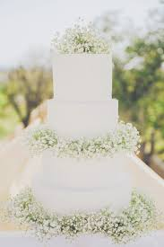 White 4 Tier Wedding Cake Decorated With Gypsophila Babys Breath Centrepieces Rustic