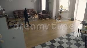 kaukasischer dieb in schwarzen kleidung und balaclava gehen im großen wohnzimmer auf der suche nach was zu stehehlen um zu steh